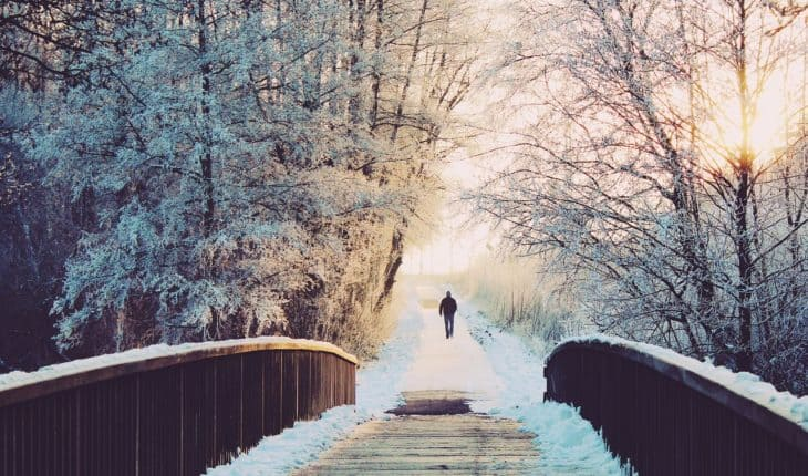 man walking on bridge in snow